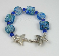 Blue glass beaded bracelet with silver starfish clasp.