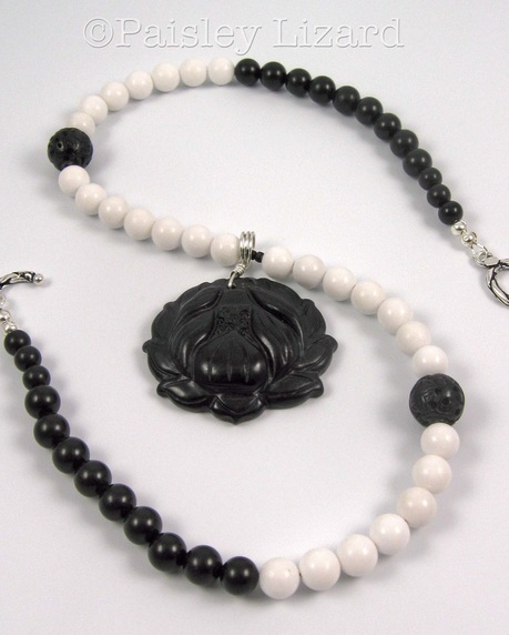 Picture of black lotus pendant on black and white beaded necklace
