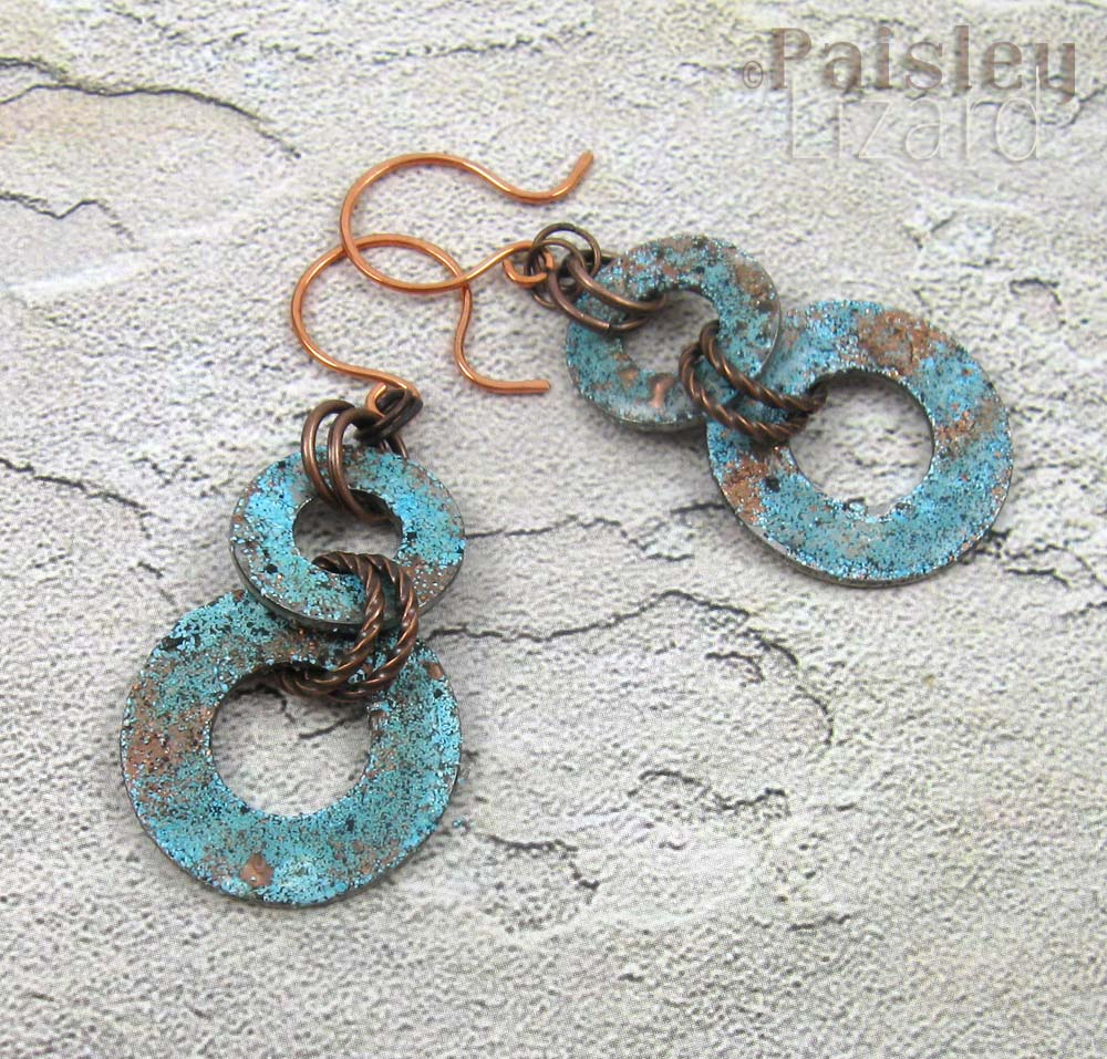 Copper patina washer earrings on sand texture background