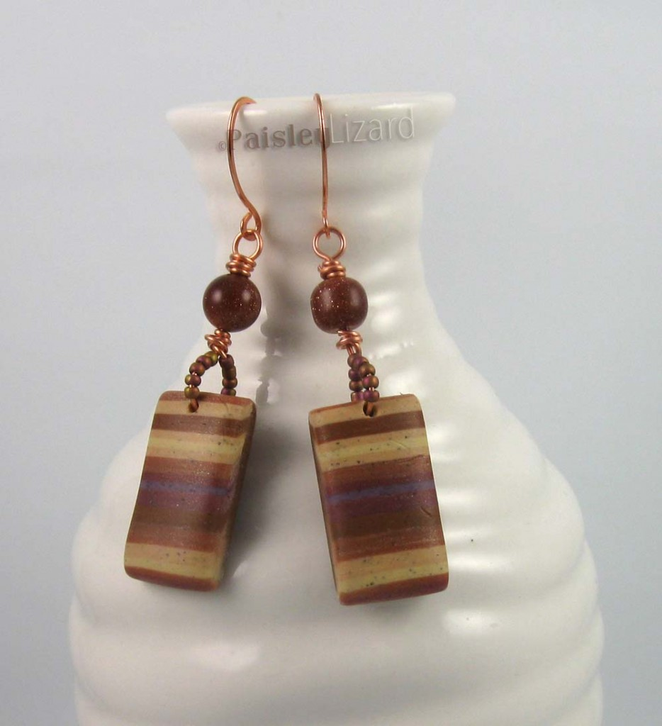 polymer clay earrings displayed on bottle
